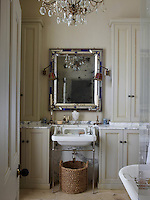 The bathroom is decorated in neutral tones and furnished in a traditional style.