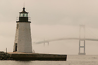 USA, Newport, RI - The Goat Island light house shows clearly in front of the fog engulfed Newport Bridge.