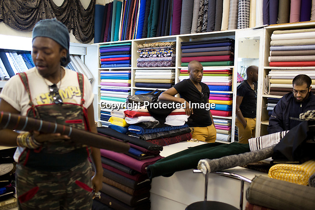 SOWETO, SOUTH AFRICA JULY 2: Lethabo Tsatsinyane and Sibu Sithole, young designers part of the group Smarteez shops or fabrics in a store on July 2, 2014 in Jabulani section of Soweto, South Africa. Soweto today is a mix of old housing and newly constructed townhouses. A new hungry black middle-class is growing steadily. Many residents work in Johannesburg but the last years many shopping malls have been built, and people are starting to spend their money in Soweto. (Photo by: Per-Anders Pettersson)