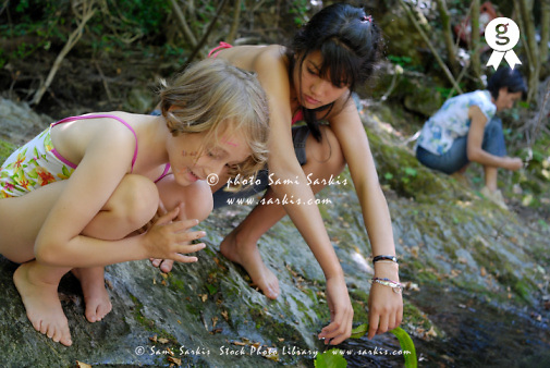 Two girls (7-14) and woman playing on river bank (Licence this image exclusively with Getty: http://www.gettyimages.com/detail/sb10065474ao-001 )