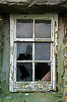 Exterior broken window of derelict croft house, Berneray, Outer Hebrides, Scotland
