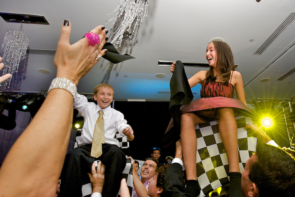 Brother and sister being lifted in chairs during the hora dance at a B'Nai Mitzvah.