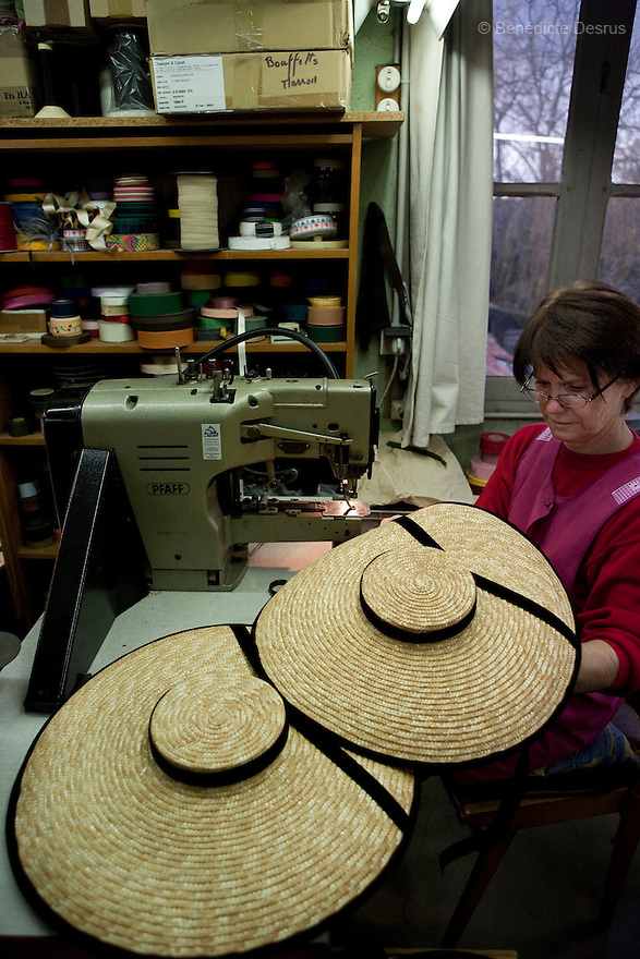 9 december 2009 - Coustilleres' hat factory, Septfonds, France - Paulette Audouy works since 15 years at the Coustilleres' hat factory. She is using specially-designed antique sewing machines for hats. Each hat is finished with lovely embellishments: ribbons, feathers, flowers or sinemay. Septfonds is the heart of French straw hat making, due to its very ancient hatter tradition. The hat making industry had its commercial peak in the late 19th century..Coustillères is a family owned hat making factory that has been making straw hats in Septfonds for nearly 100 years. They make hats from straw, felt, and cloth as well as caps. The current owner is Jean-Claude Coustilleres. He is one of the last hat makers of the region..The straw hat making process is very labor intensive and numerous hands are involved. Nearly all of the equipment is over 100 years old, they use the original presses and tools including aluminium molds and sewing machines and dye their own straw continuing the traditional methods of manufacturing. The hat blocking and shaping, straw braids construction and dyeing are all done by hand..The company works on behalf of fashion houses and makes a variety of regional and historical hats. It produces 2 collections a year distributed by a network of salespeople and through a catalog to clients around the world. Photo credit: Benedicte Desrus