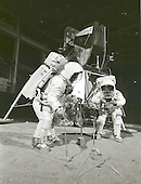 Houston, TX - (FILE) -- Two members of the Apollo 11 lunar landing mission participate in a simulation of deploying and using lunar tools on the surface of the Moon during a training exercise on April 22, 1969. Astronaut Buzz (Aldrin Jr. on left), lunar module pilot, uses a scoop and tongs to pick up a soil sample. Astronaut Neil A. Armstrong, Apollo 11 commander, holds a bag to receive the sample. In the background is a Lunar Module mockup..Credit: NASA via CNP