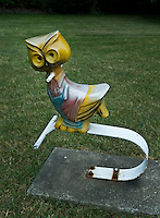 Owl antique cast aluminum spring ride in park near public swimming pool