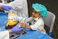 Nederland Amsterdam 2015 11 10 . Teddy Bear Hospital in het AMC  ziekenhuis.  Teddy Bear Hospital (TBH) is één van de grootste projecten van IFMSA-NL. Het TBH is een rollenspel. Dat houdt in dat kleuters van vier t/m zes jaar als 'vader' of 'moeder' hun beer of een andere knuffel meenemen naar een nagebootst ziekenhuis. Geneeskundestudenten spelen voor arts en behandelen de 'patiënten'. Het doel van Teddy Bear Hospital is om kinderen op een speelse manier kennis te laten maken met de gezondheidszorg, om zo de angst voor dokters en het ziek-zijn enigszins weg te nemen. Bovendien leert het medische studenten om te gaan met kinderen en trainen ze hun communicatieve vaardigheden. De gipskamer. Foto Berlinda van Dam / Hollandse Hoogte