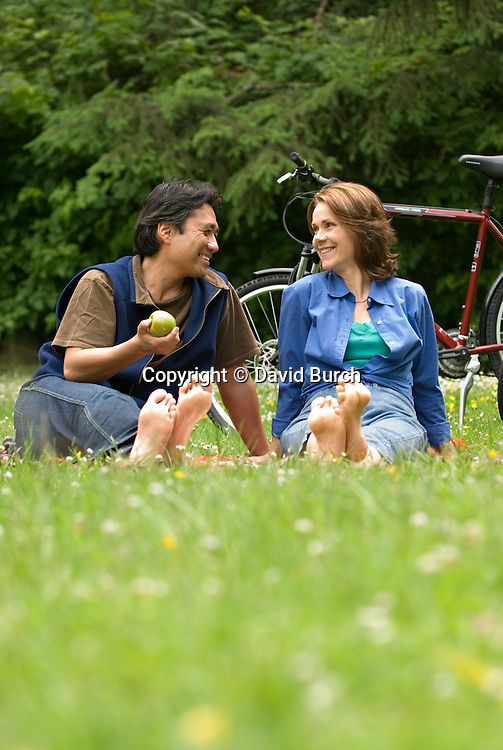 Couple barefoot  and laughing  in meadow with bikes