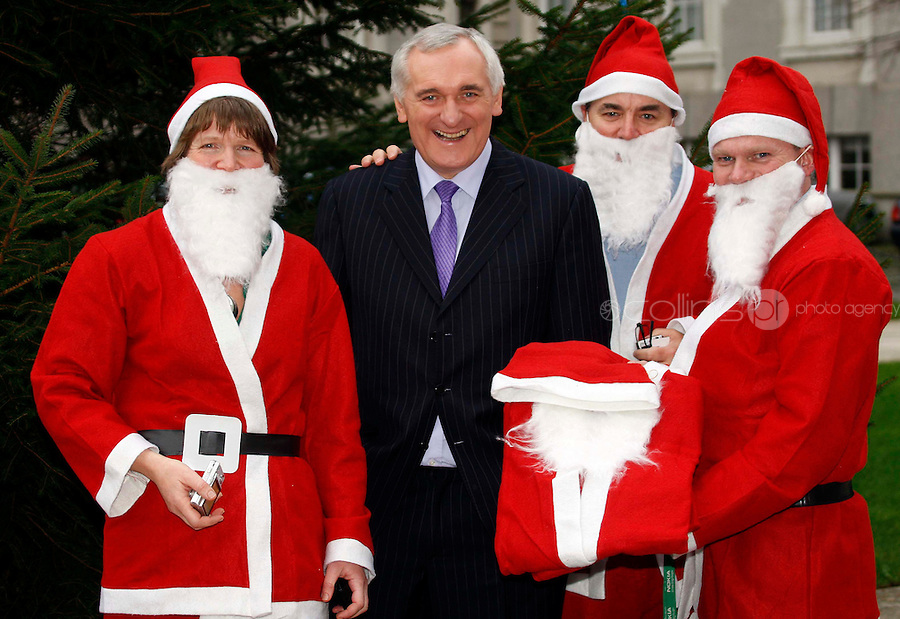 06/12/'07 Taoiseach Bertie Ahern is presented with a Santa outfit pictured at Government Buildings with three of the Santas who are part of an attempt  to set a new World Record. The Santas are part of a World record attempt to have 10,000 Santas man the city of Derry's Walls on the 9th of December 2007, no later than 11.15am. The aim will be to raise money for local charities - and to get the Maiden City into the Guinness Book of Records. There will also be attempst in Liverpool, Las Vegas and Glasgow over the coming weeks....Picture Collins, Dublin, Colin Keegan.