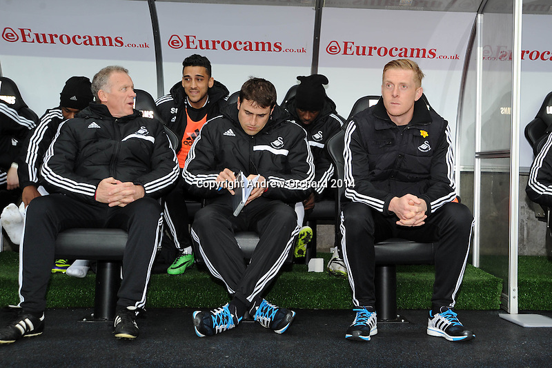 Swansea city's manager Garry Monk (r) with his coaching staff sits in dugout ahead of k/o. Barclays Premier league, Swansea city v Crystal Palace match at the Liberty Stadium in Swansea, South Wales on Sunday 2nd March 2014.