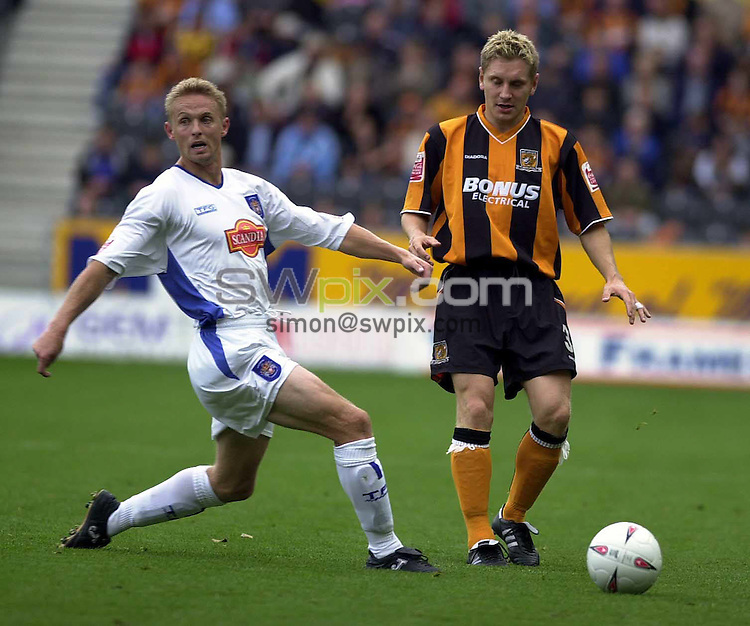 Pix: Chris Whiteoak/SWpix.com. Football, Coca-Cola League 1, Hull City v Stockport County. 25/09/2004...COPYRIGHT PICTURE>>SIMON WILKINSON>>01943 608782>>..Hull's Andy Dawson manages to just get his pass away before Stockport's Lee Cartwright gets there