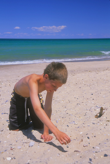 A child probes the sand for a Petosky Stone, a stone with fossile elements in it that is polished and sold at local tourist stores, on the sandy shore of Cathead Bay on the Leelanau Peninsula in Leelanau State Park, Leelanau County, Michigan