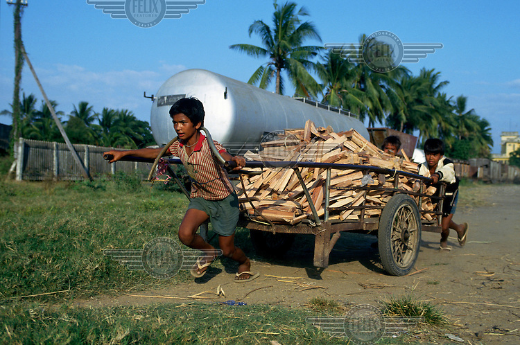 Boys with a cart laden with bits of wood they have collected at the city railway station.