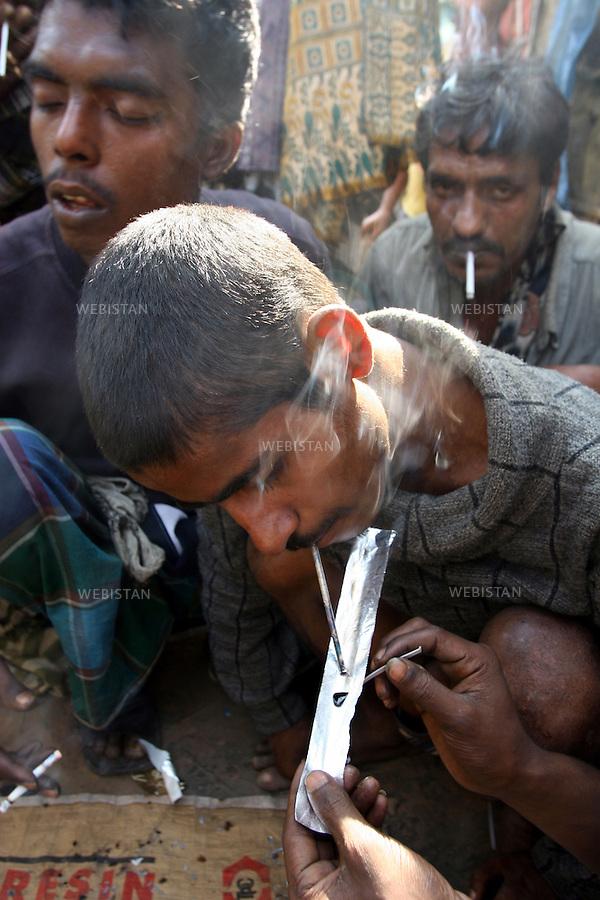 2006. Bangladesh, Dhaka. Drug users smoke a dose a of heroin...2006. Bangladesh, Dhaka.  Des toxicomanes fument une dose d'héroïne.