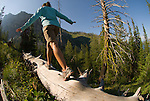 A young woman balances on a log while hiking in Grand Teton National Park, Jackson Hole, Wyoming.