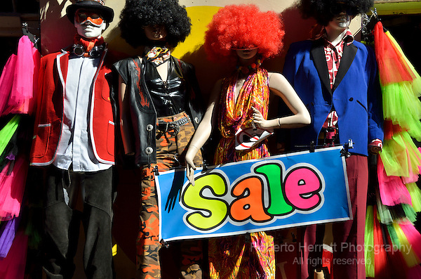 Multicoloured 'Sale' sign and mannequins on a market fashion stall