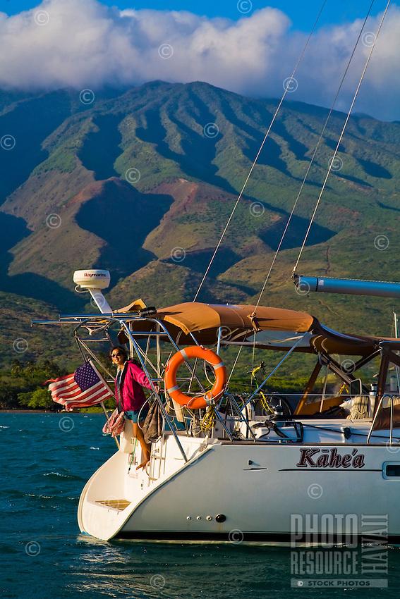 Woman on stern of cruising sailboat at anchor off Molokai, Hawaii