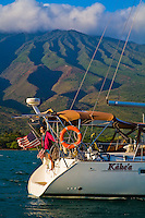 Woman on stern of cruising sailboat at anchor off Molokai, Hawaii