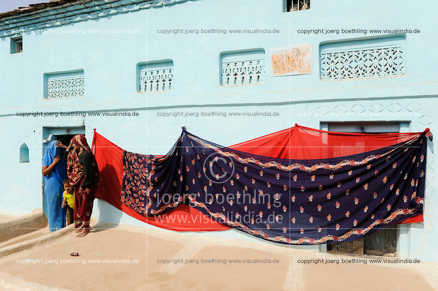 INDIEN Uttar Pradesh, Frauen unterer Kasten und Kastenlose Frauen in Doerfern in Bundelkhand, Saris trocknen an der Hauswand / INDIA Uttar Pradesh low caste and dalit women in villages in Bundelkhand, sari dry at house wall