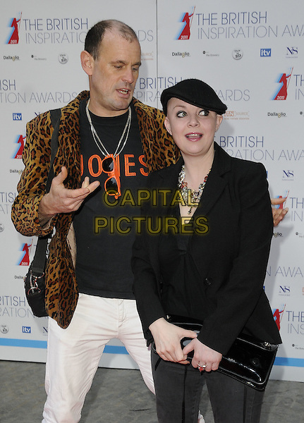 MARK JONES & GAIL PORTER.The British Inspiration Awards 2011, The Brewery, Chiswell St., London, England..April 8th, 2011.half length black jacket jeans grey gray bag purse necklace bald hat adjusting funny white yellow brown leopard print mouth open.CAP/CAN.©Can Nguyen/Capital Pictures.
