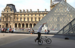 Boy performing on his bike outside the Louvre museum Paris.