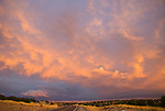 Pink clouds from passing autumn storm glow orange, pink, red and radiate across the southwestern horizon at sunset, New Mexico