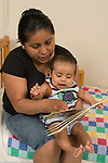 3 month old baby boy with mother intereested in and excited by board book she is showing him