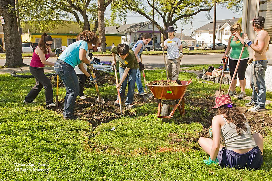Young women and young men students volunteer to dig with shovels and load wheelbarrow in yard of New Orleans home in the 9th ward to develop a water drainage system for houses