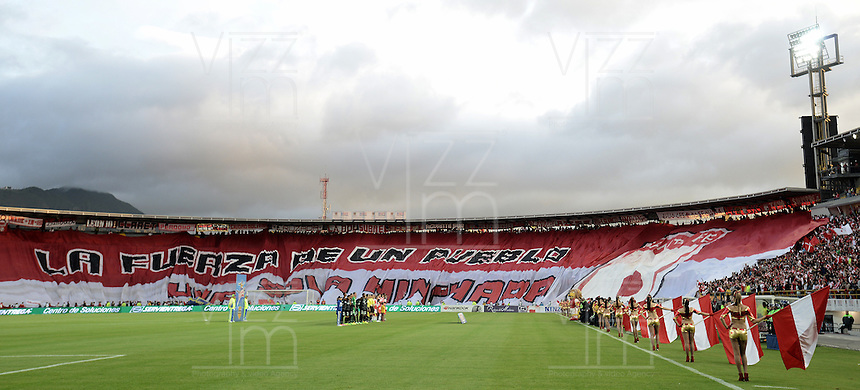 BOGOTÁ -COLOMBIA, 16-11-2014. Hinchas de santaFe exitienden una bandera gigante de su equipo durante los actos protocolarios previo al encuentro entre Independiente Santa Fe y Atlético Nacional por la fecha 1 de los cuadrangulares finales de la Liga Postobón II 2014 jugado en el estadio Nemesio Camacho El Campín de la ciudad de Bogotá./ Followers of Santa Fe extend a big flag of their team during the formal events prior of the match between Independiente Santa Fe and Atletico Nacional for the first date of the final quadrangular of the Postobon League II 2014 played at Nemesio Camacho El Campin stadium in Bogotá city. Photo: VizzorImage/ Gabriel Aponte / Staff