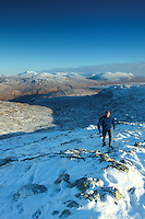 A walker ascending Stob Mhic Mhartuin in winter overlooking The Mamores and Blackwater Reservoir, Glencoe, Highland<br /> <br /> Copyright www.scottishhorizons.co.uk/Keith Fergus 2011 All Rights Reserved