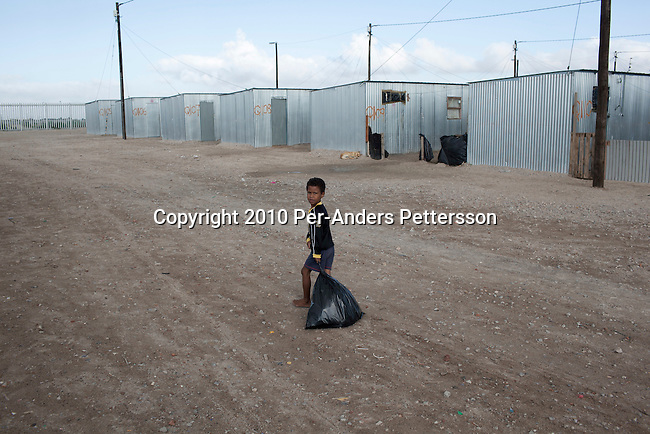 "CAPE TOWN, SOUTH AFRICA - MAY 3: A child pulls a trash bag next to tin houses on May 3, 2010, in Blikkiesdorp about 40 kilometers south of Cape Town, South Africa. Blikkiesdorp, which is Afrikaans for ""Tin Can Town"", was given its name by its residents because of the row-upon-row of tin-like shacks made of corrugated iron. It was built by the City of Cape Town in 1997 and about 1600 one-roomed shacks were built. It has been known for its bad conditions and a dumping ground for shack dwellers from other areas around Cape Town. Recently many street people in Cape Town has been forcefully removed and relocated to this place. The ones that have refused has been put in holdings cells or prisons such as Pollsmoor Prison. This campaign has  identified in the preparation for the soccer World Cup, who starts on June 11, 2010 and goes on for a month. The City of Cape Town doesn't want international visitors to be hassled by street people. (Photo by Per-Anders Pettersson)"
