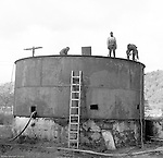 Lawrenceville PA: Location photography at the Atlantic Refining site at 5733 Butler Street. View of  workmen making repairs on a small tank.<br /> This track of land has been involved in oil-related refining for over 100 years.  ARCO sold the property to SUNOCO which still operates a storage facility at 5733 Butler Street.