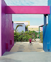 Stepping stones set in a gravelled terrace are a fun place to play and bright pink and blue painted concrete walls create a cheerful ambience in the sheltered courtyard garden