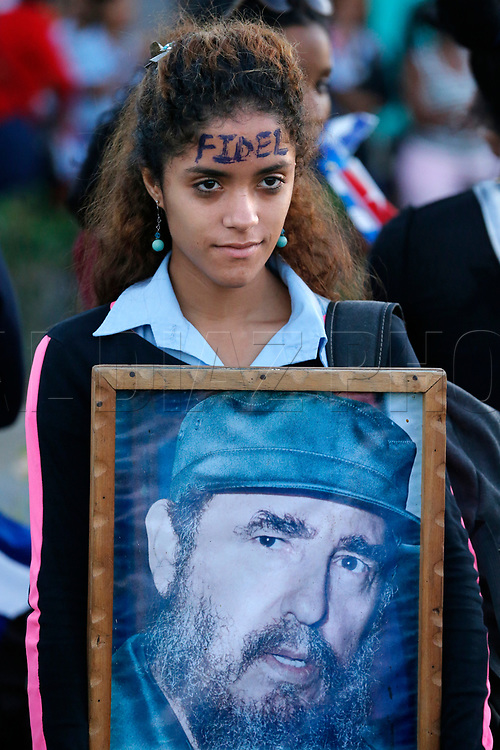 A young woman waits for the arrival of the caravan carrying the ashes of Fidel Castro on the road to Cemeterio Santa Ifigenia in Santiago de Cuba on Sunday, December 4, 2016