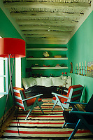 The small winter living room is painted a vibrant green and has chairs upholstered in bright orange
