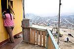 A woman talks to her neighbors on Wednesday, Apr. 8, 2009 in Ventanilla, Peru.