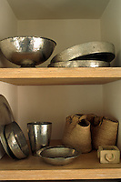Locally crafted metal bowls, platters and other vessels are stored on open shelving in the kitchen