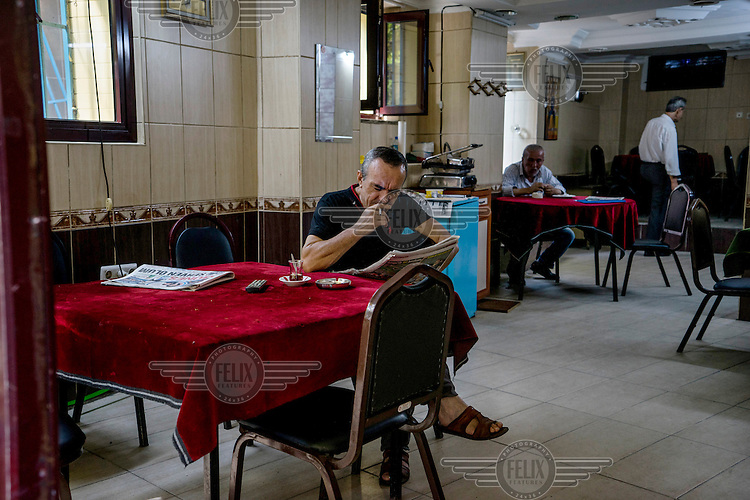 At a small Cafe in Karakoy a man smokes a cigarette while reading a newspaper.