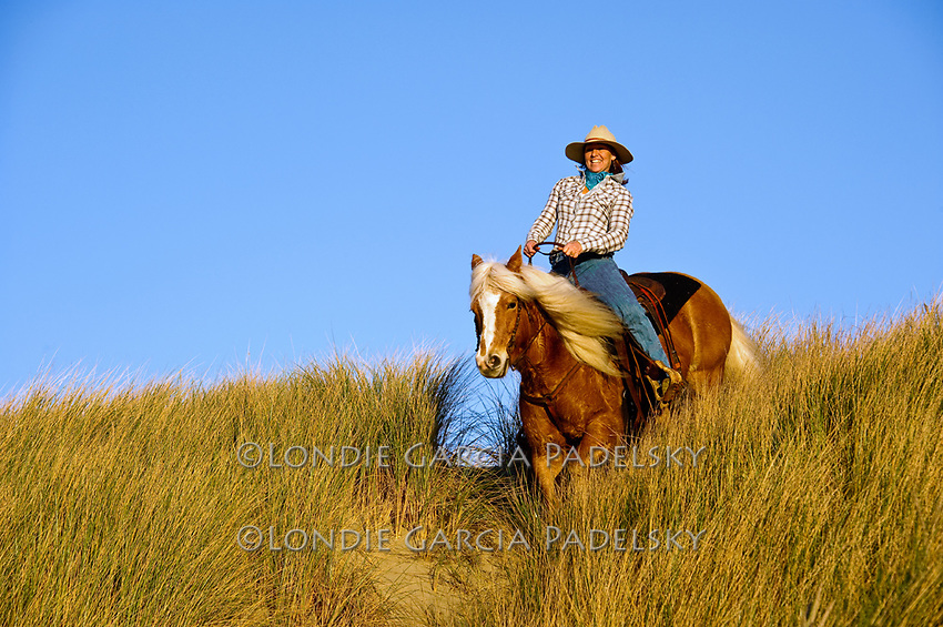 Cowgirl riding horseback and leading a horse on the sand dunes. Central Coast of California