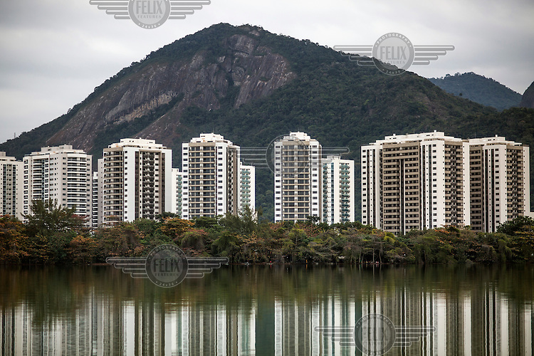 A view of the Athlete's Village across the green-tinged waters of the sewage-filled Lagoa da Jacarepagua, one of the many inter-connected lagoons that, as developement in the area grows, are increasingly pollututed by raw sewage and waste.<br />  <br /> <br /> The authorities and private developers have poured billions of dollars into transportation projects, hotels, a residential complex to house the athletes and a vast Olympic Park where nearly half the sports will be played in Rio's expansive neighbourhood, Barra da Tijuca. <br /> <br /> Those improvements join the private schools, gated communities, and other consumer culture that attracts middle-class families tired of run-down feel of Rio's older neighbourhoods. <br />  <br /> However, the breakneck development has brought problems similar to those of which its new residents were fleeing, including congested traffic and untreated sewage in what was supposed to be a new model for urban living.