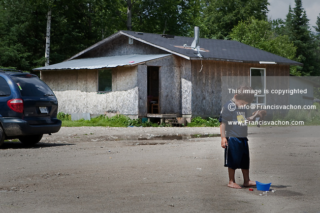 A young aboriginal plays in front of a modest house in the algonquin Anicinape community of Kitcisakik in Quebec, Canada, July 18, 2009. The aboriginals living in Kitcisakik, a small algonquin Anicinape community, don't have an official statue and are considered squatters by the crown. They don't have access to electricity and running water in their houses that are very modest.