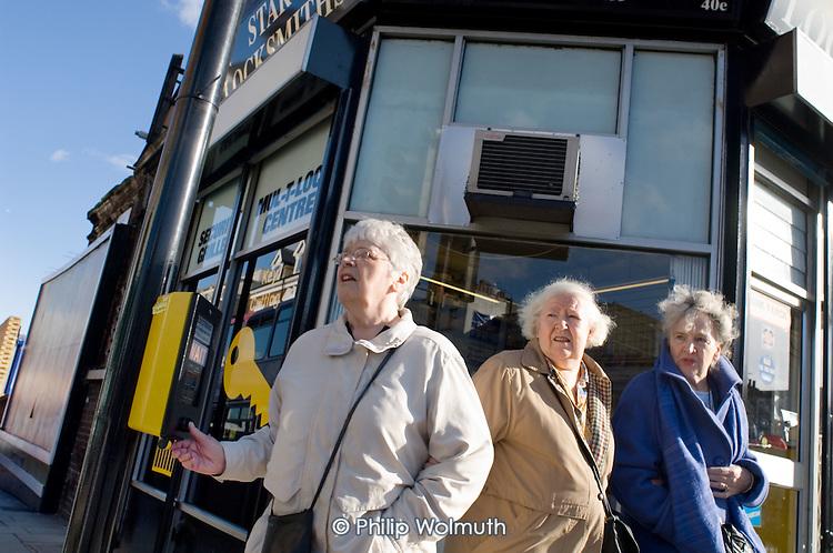 Three elderly women wait to cross a busy road in Kilburn, London.