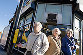 Three elderly women wait to cross a busy road in Kilburn, London.