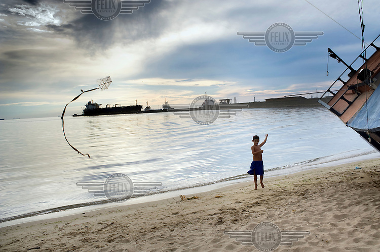 A boy flys a kite on a beach at Punto Fijo. Beyond the boy oil tankers wait to take on loads at the world's largest oil refinery.