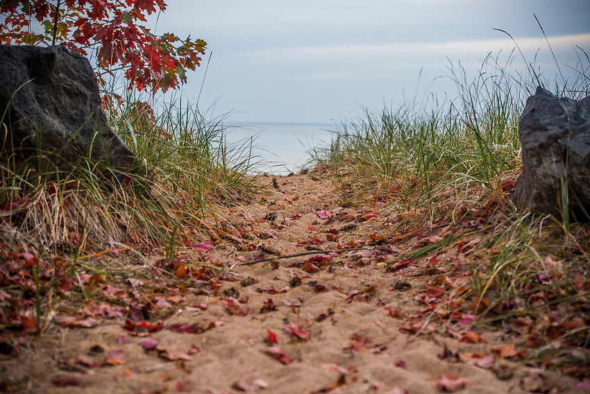 Lake Superior beach path with fallen red leaves in autumn at Marquette, Michigan.