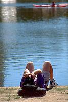 Man age 24 soaking up sun rays on waterfront at Loring Park.  Minneapolis  Minnesota USA