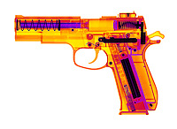 An X-ray of an air gun.  This gun shoots plastic pellets by air pressure.  The gun is designed to be the same weight and size as a real hand gun.  This is a false color x-ray.