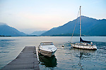 Two sailboats and a dock at dusk on Lake Como, Italy in front of the northern lake town of Gravedona