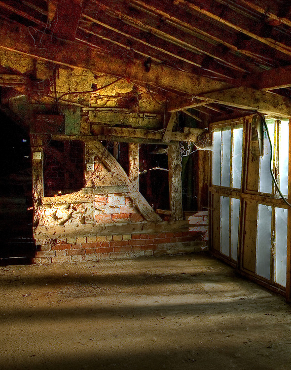 An interior view of an old disused thatched barn with sunlight shining  through glazed windows onto