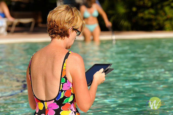 Sheridan Desert Oasis. Woman reading on I-Pad by swimming pool.