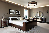 A luxurious spacious bedroom with panelled taupe walls. The room is furnished a dark wood king-size sleigh bed, bedside chest of drawers and dressing table.